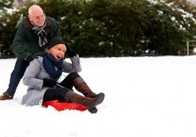 Smiling elderly man  pushing his wife on sled in snowy park