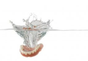 Single set of orthodontic dentures falling into clear water with stop motion splash over white background